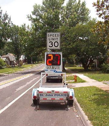 Traffic speed monitor on a neighborhood street showing 30 miles per hour speed limit
